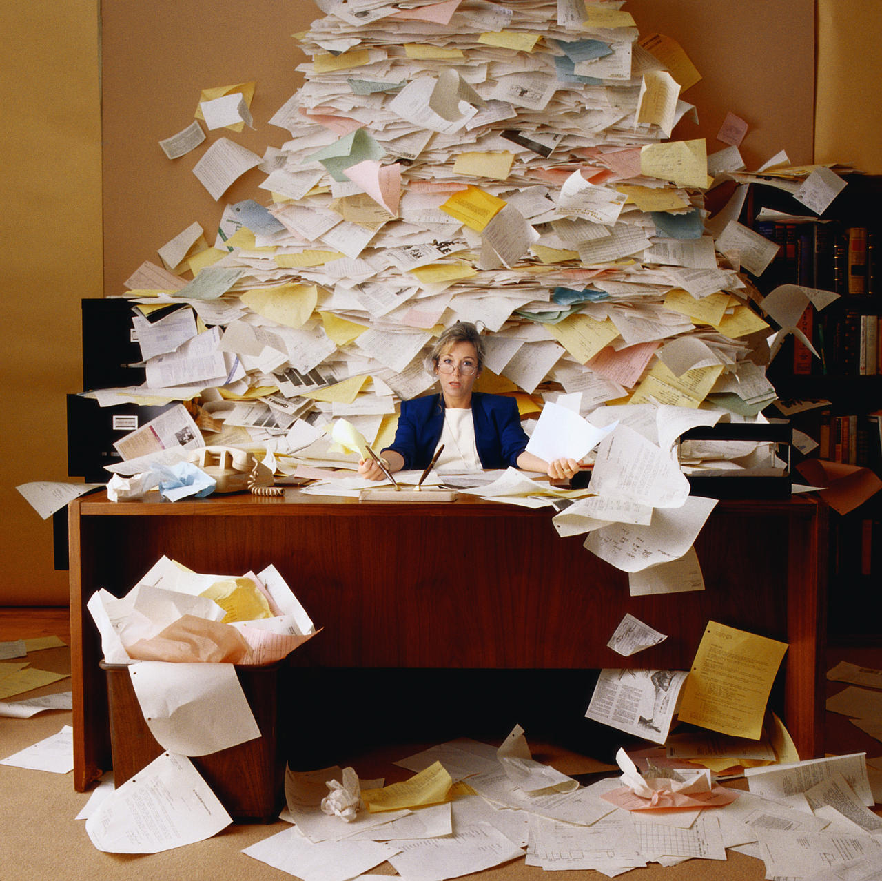 Messy desk with high stack of paper